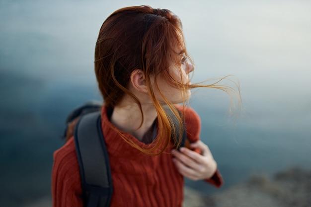 Kobieta z plecakiem w górach na zewnątrz w pobliżu morza odwróciła przycięty widok modelu