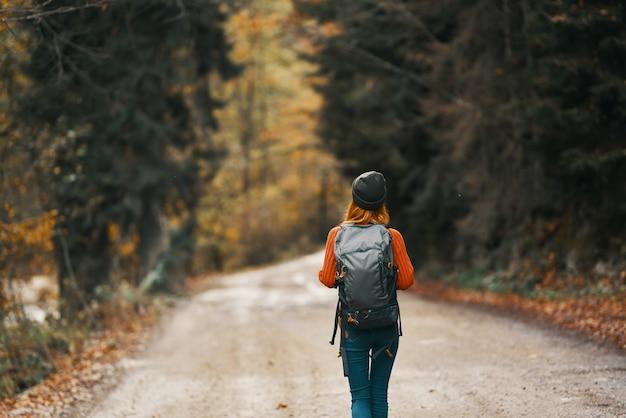 Kobieta z plecakiem w kapeluszu i pomarańczowym swetrze na drodze w jesiennym lesie