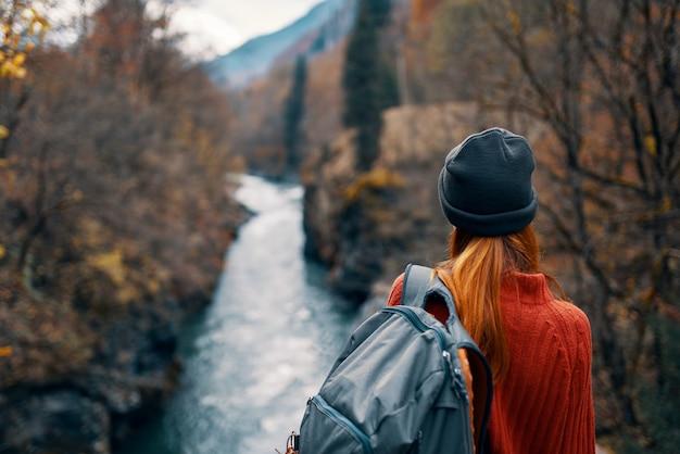 Kobieta z plecakiem w naturze na moście w pobliżu przygody w górach rzeki