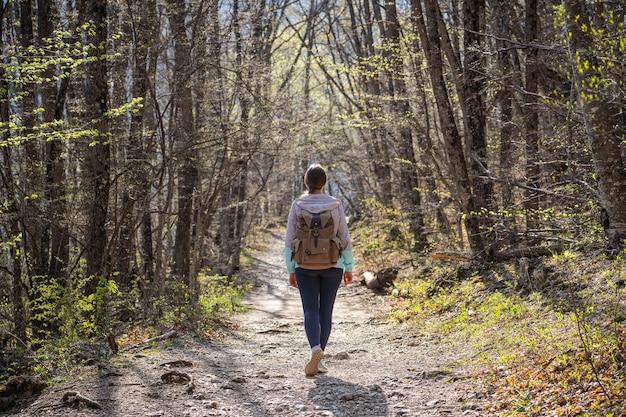 Kobieta z plecakiem wybrała się na leśną wycieczkę. piesze wycieczki i przetrwanie. leśny szlak.