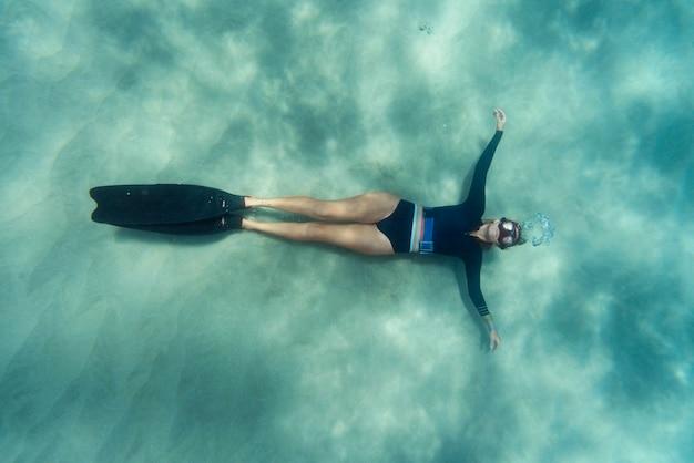 Kobieta z płetwami pływanie w oceanie