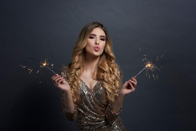 Kobieta z płonącymi ogniami dmucha buziaka
