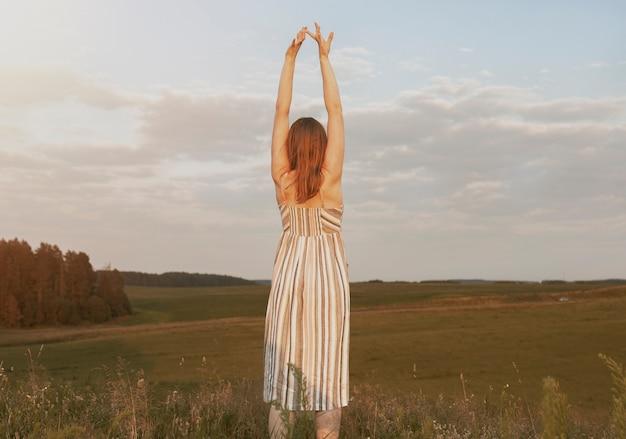 Kobieta z podniesionymi rękami na letnim polu ciesząca się wolnością i krajobrazową przyjemnością bycia wolnym w ...