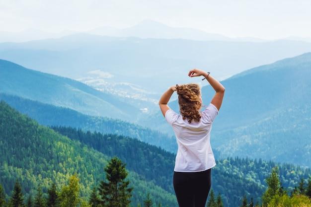 Kobieta z podniesionymi rękami na tle malowniczych gór. kobieta czuje się szczęśliwa w górach