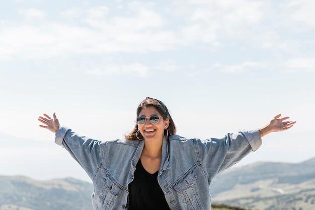 Kobieta z podniesionymi rękami stojąc na skale
