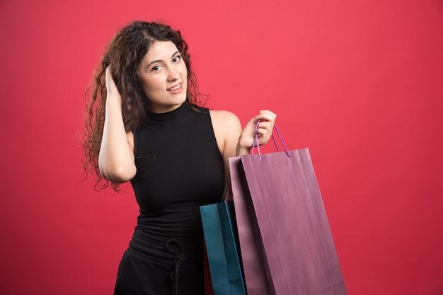 Kobieta z podstępnym spojrzeniem trzymając torby na czerwonym tle