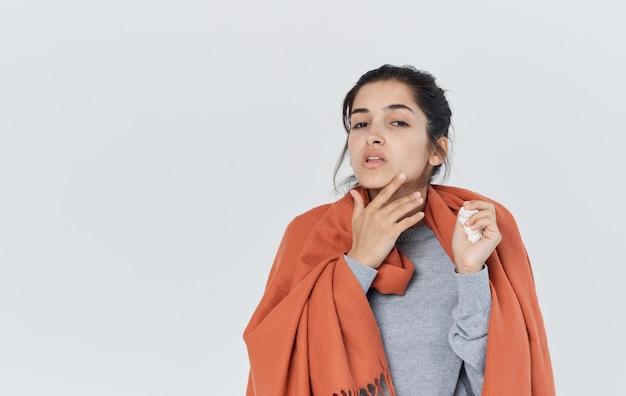 Kobieta z pomarańczowym czołem na ramionach trzyma serwetkę w ręku problemy zdrowotne filiżanka herbaty przycięty widok. wysokiej jakości zdjęcie