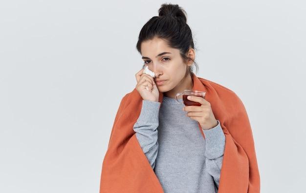 Kobieta z pomarańczowym czołem na ramionach trzyma serwetkę w ręku problemy zdrowotne filiżanka herbaty przycięty widok.