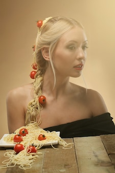 Kobieta z pomidorami i spaghetti w jej włosy