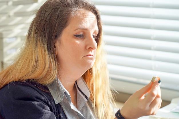 Kobieta z powątpiewaniem trzyma obrączkę