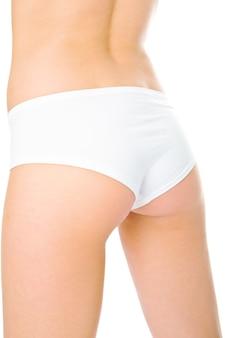 Kobieta z powrotem w białych spodniach na białym tle