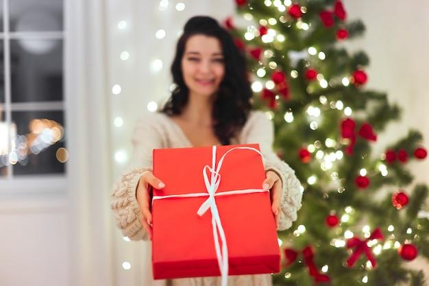 Kobieta z prezentem w pudełku prezentowym w pobliżu choinki w domu