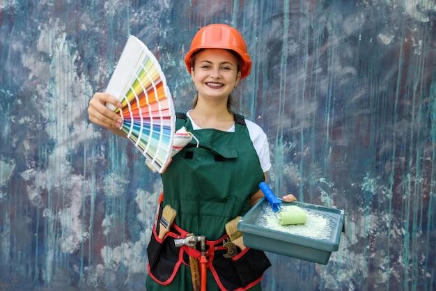 Kobieta z próbką koloru. ona jest w kombinezonie i hełmie, pozowanie na abstrakcyjnym tle