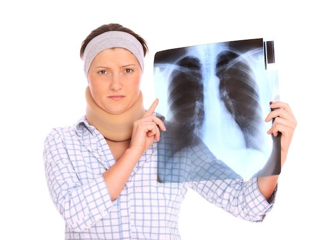 Kobieta z problemami z kręgosłupem trzymająca zdjęcie rentgenowskie nad białym