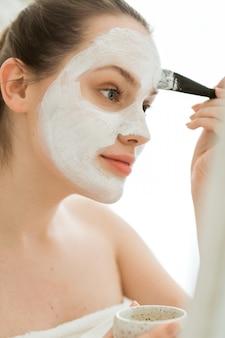 Kobieta z produktem kosmetycznym, maska na twarz