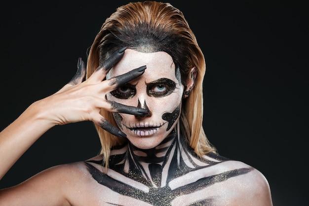Kobieta z przerażającym makijażem halloween na czarnym tle
