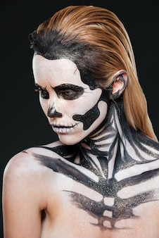 Kobieta z przerażającym przestraszonym makijażem na czarnym tle