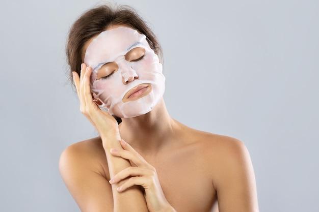 Kobieta z prześcieradłem nawilżającą maską na jej twarzy odizolowywającej na szarość