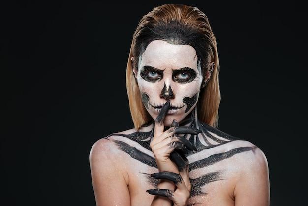 Kobieta z przestraszonym halloweenowym makijażem pokazująca gest ciszy na czarnym tle