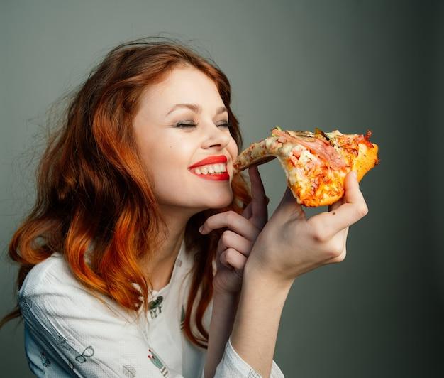 Kobieta z przyjemnością je pizzę