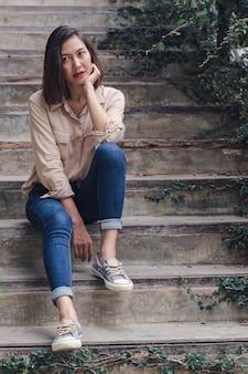 Kobieta z przyjemnością siedziała przy starych schodach.
