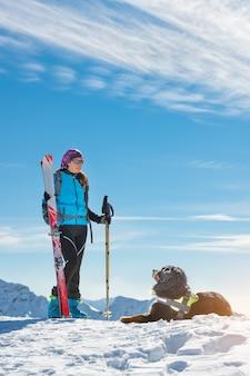 Kobieta z psem berneńskim w górach na niebie