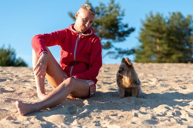 Kobieta z psem na piasku, w słońcu. w dowolnym celu.