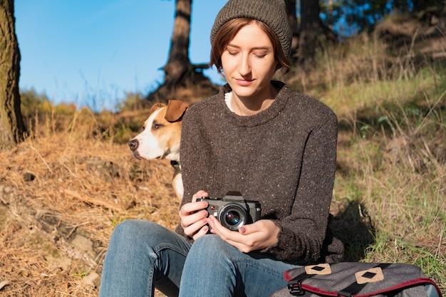 Kobieta z psem trzymając filmową kamerę w piękny jesienny dzień. młoda turystka siedzi pod sosnami w słoneczne popołudnie i cieszy się dobrą pogodą
