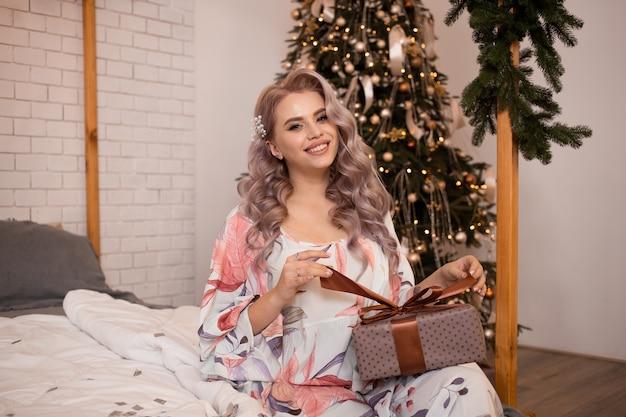 Kobieta z pudełkiem w domu w sypialni w czasie świąt bożego narodzenia