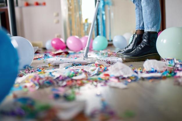 Kobieta z pushbroom sprzątanie bałaganu podłogi w pokoju po imprezie konfetti, rano po przyjęciu, prace domowe, sprzątanie