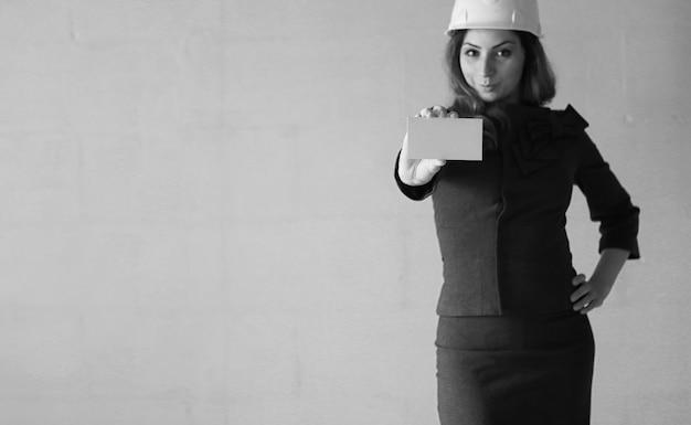 Kobieta z pustą kartką papieru w ręku na budowie