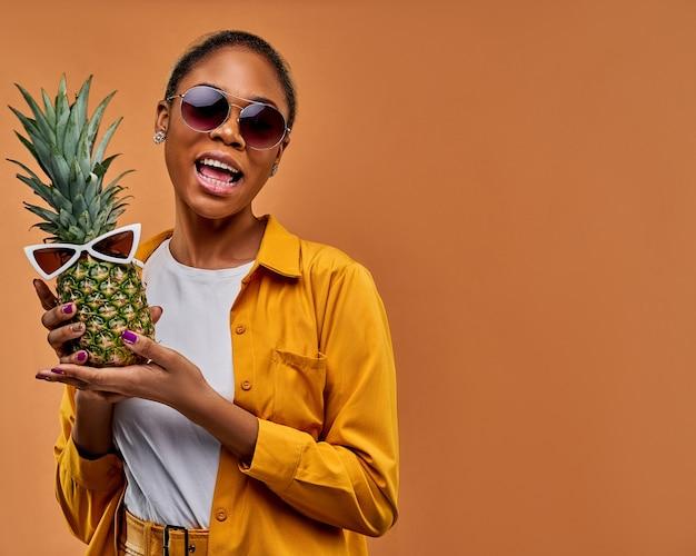 Kobieta z radosnym uśmiechem w okularach przeciwsłonecznych w żółtej koszuli pokazuje zielonego ananasa w białych okularach przeciwsłonecznych. koncepcja podróży