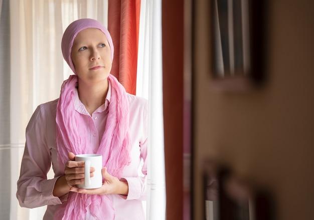 Kobieta z rakiem i różowym szalikiem na głowie pije kawę i wygląda przez okno