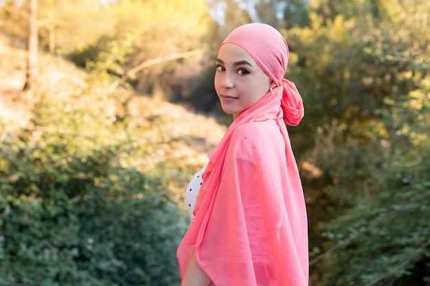 Kobieta z rakiem na sobie różowy szalik patrząc wojownik