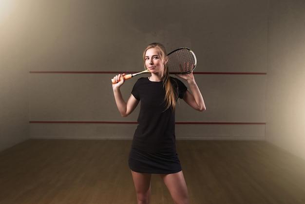 Kobieta z rakietą do squasha, kryty klub szkoleniowy