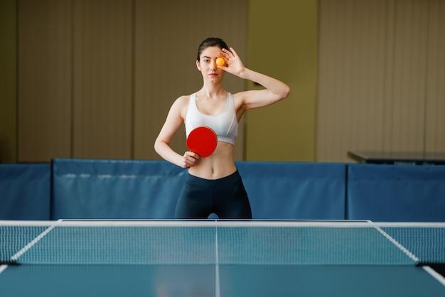 Kobieta z rakietą pokazuje pomieszczeniu do ping ponga.