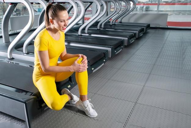 Kobieta z rannych kolana siedzi w siłowni uczucie bólu
