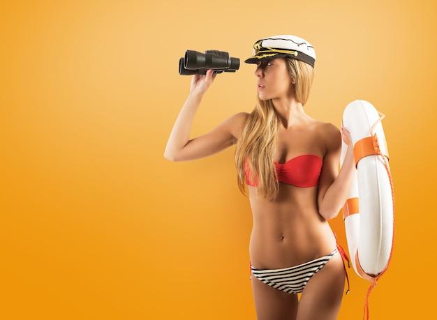 Kobieta z ratownikiem patrząc na morze z lornetką na żółto