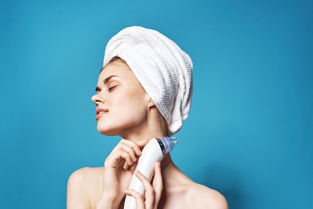 Kobieta z ręcznikiem na głowie czyszczenie twarzy pielęgnacja skóry niebieskim tle. zdjęcie wysokiej jakości