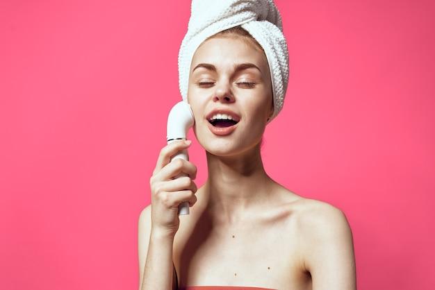 Kobieta z ręcznikiem na głowie czyszczenie twarzy pielęgnacja skóry różowym tle