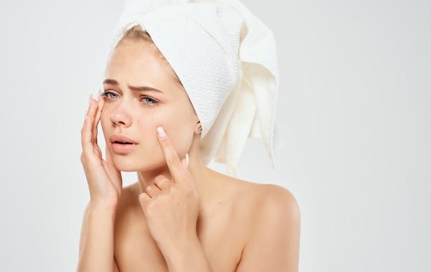 Kobieta z ręcznikiem na głowie dotyka twarzy rękami zapalonymi na świetle.