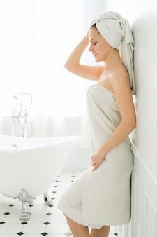 Kobieta z ręcznikiem na głowie i ciele po prysznic