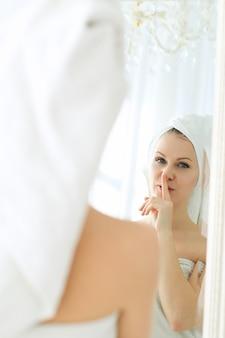 Kobieta z ręcznikiem na głowie i ciele po prysznicu