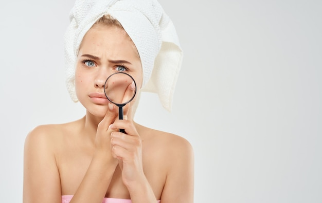 Kobieta z ręcznikiem na głowie lupa w ręku nagie ramiona kosmetologia dermatologia.