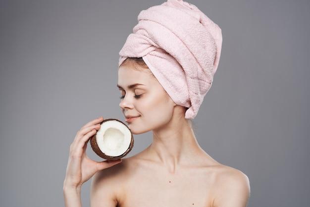 Kobieta z ręcznikiem na głowie nagie ramiona kokos w dłoni