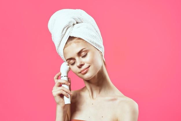 Kobieta z ręcznikiem na głowie nagie ramiona kosmetologia masażer do twarzy