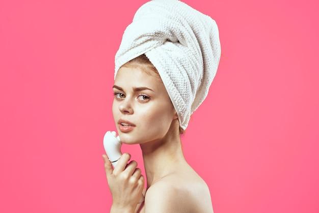 Kobieta z ręcznikiem na głowie nagie ramiona kosmetyki medycyny masażu. zdjęcie wysokiej jakości