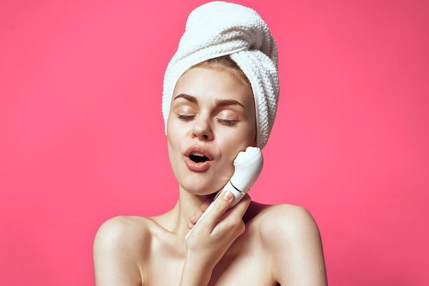 Kobieta z ręcznikiem na głowie nagie ramiona masaż twarzy