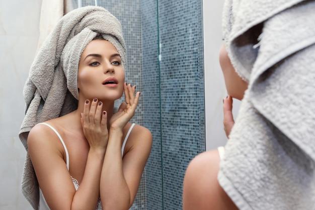 Kobieta z ręcznikiem na głowie, patrząc w lustro i stosując makijaż