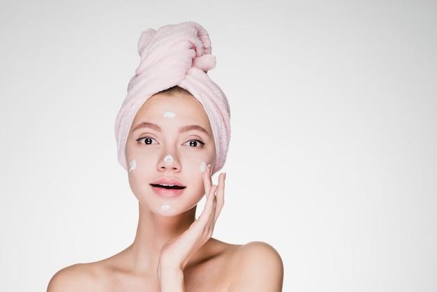 Kobieta z ręcznikiem na głowie po prysznicu nakłada krem na twarz na szarym tle